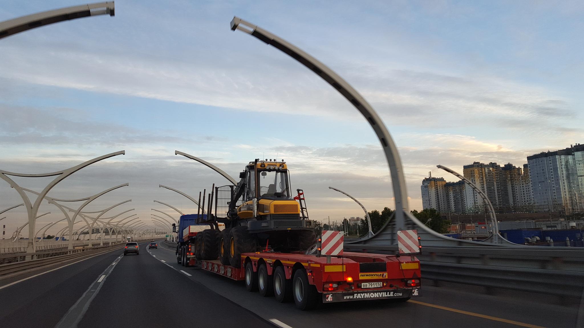 Перевозка строительной техники по России – тяжеловесный низкорамный трал на мосту